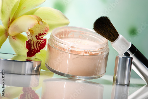 opened face powder, brush and blooming yellow orchid