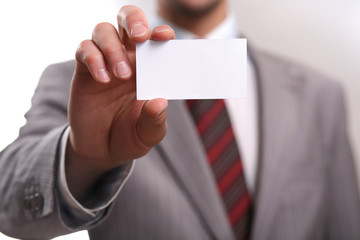 businessman holding out a blank business card.