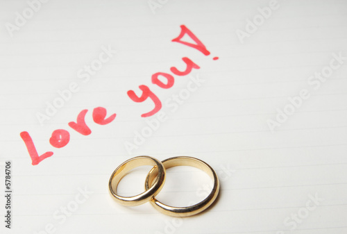 Loving letter with golden wedding rings
