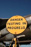 danger sign in front of vintage military jet poster