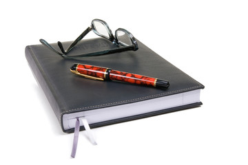 Black bound note pad with reading glasses and fountain pen