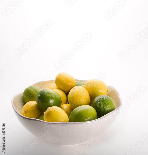 Bowl of lemons and limes on white.