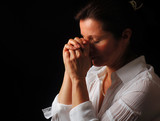 Beautiful woman with eyes closed in fervent prayer