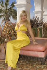 Beautiful Blond sitting outdoors in a Yellow dress