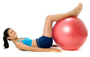 A pretty young slim Asian woman exercising with a red fitball