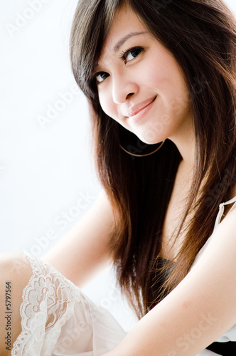 A cute young Asian teenager in white dress on white background