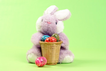 Easter bunny with wooden basket full of easter eggs
