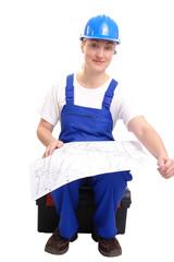 Female builder in blue jumpsuit studying building plan