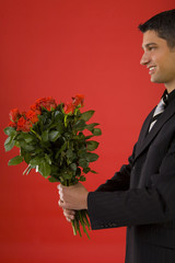 Handsome and smiling businessman with bouquet of roses