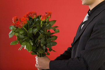 Businessman with bouquet of roses in hands.