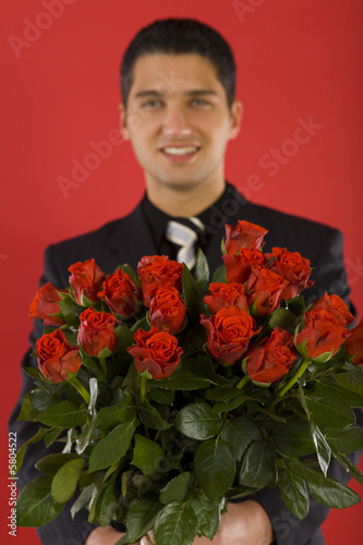 Handsome businessman with bouquet of roses in hands.