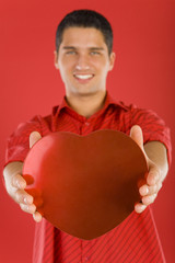 Handsome man in red shirt in strips, holding heart-shaped box