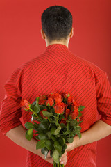 Man in red shirt in strips, holding bouquet of roses behind
