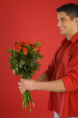 Handsome man in red shirt in strips, holding bouquet of roses.