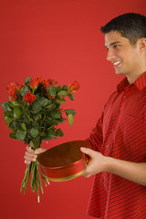 Handsome man in red shirt in strips, holding bouquet of roses