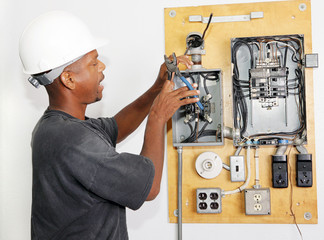 Electrician crimping a wire in an electrical panel.
