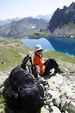 girl hiker on a rest looking at big mountain lake. poster