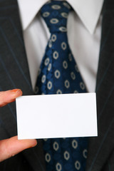blank business card in color white in front of suit and tie