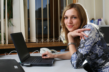 Young woman in office, laptop computer on table