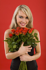 Beautiful woman in black dress, holding bouquet of roses.