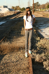 Young woman walkgin on railroad tracks