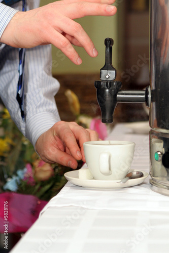 Man`s hand holding tea cup  and pouring from canister