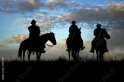 trzy-kowboje-na-koniu-sylwetkowym-przeciw-jutrzenkowemu-niebu