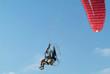 Paramotor, a motorized paraglider, flying. Blue sky background