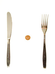 One cent lying between fork and knife