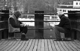 Couple sitting together on a jetty, gazing at a river view poster