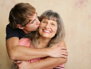 Young adult/late teen son kissing his mother on the cheek.