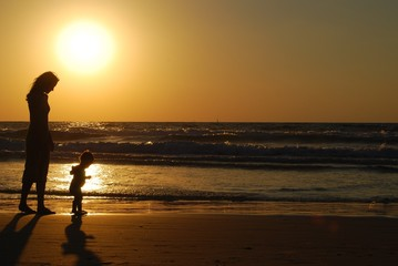 young woman with small child on the sea shore on sunset