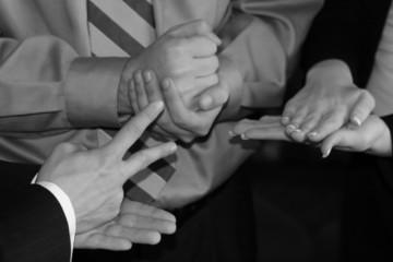 Three businesspeople's hands playing hands, rocks, scissors