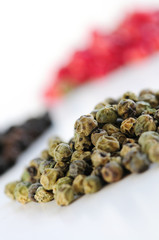 Heaps of assorted peppercorns on white background