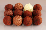 Several assorted chocolate truffles in rows on brown background poster