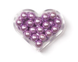 Heart-shaped plastic box with pink pearls in it. poster