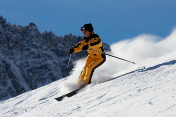 skier woman in yellow suite with clouds of snow powder