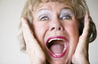 Close-up of a senior woman with her mouth open screaming.