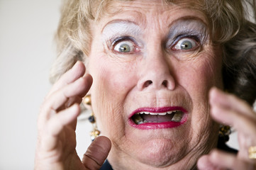 Close-up of a horrified senior woman with her mouth open.