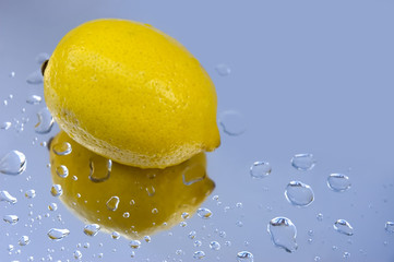 Single fresh lemon and water drops on reflecting surface