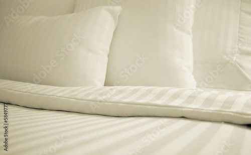 Bed with set of crisp striped sheets and pillows
