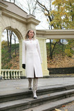 beautiful young woman in a white coat costs on a step poster