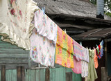 The bed-clothes to be dried on a cord in a village poster