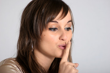 girl asking for silence with finger on lips