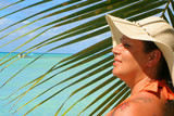 voluptuous woman  with palm backdrop on a tropical beach poster