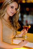 Beautiful blond woman waiting at bar counter poster