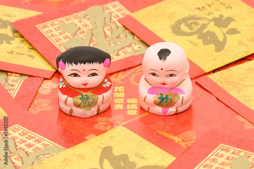Traditional Chinese boy and girl figurines on red packets