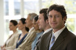 Confident businessman with team seated in line with him
