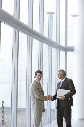 Two businessmen shaking hands in front of large glass windows