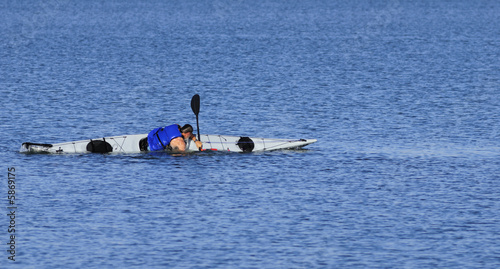 A powerful male kayaker performs float-asisted roll